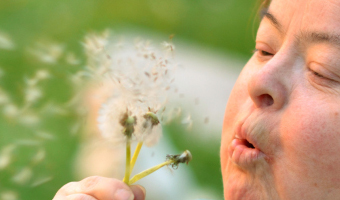 Kind mit Down Syndrom bläst in Pusteblume